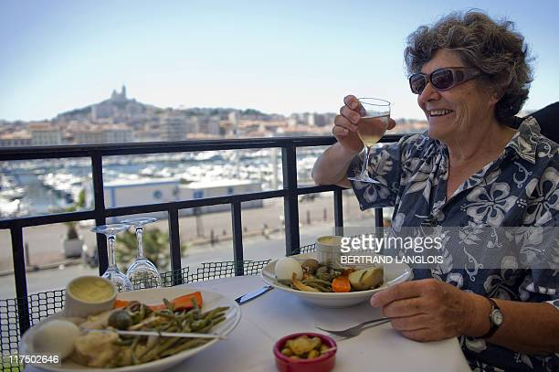 People eat an aioli at a restaurant of the Vieux Port harbour in Marseille southern France on June 27 2011 AFP PHOTO / BERTRAND LANGLOIS