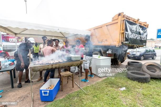 People eat at a barbecue at a road block on March 26 in Cayenne French Guiana during a string of regionwide protests and road blockades Road...