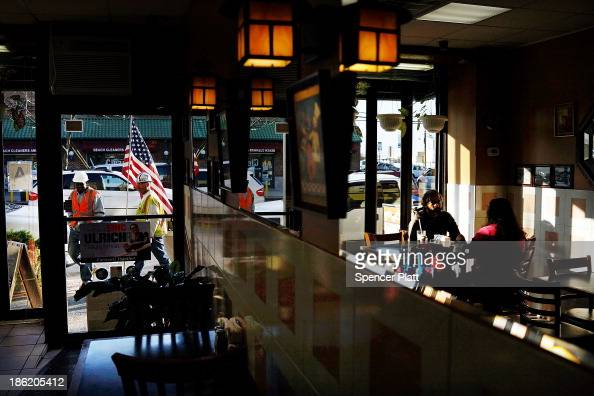 People eat breakfast at a cafe that opened at Rockaway Beach following the devastation of Hurricane Sandy on October 29 2013 in the Queens borough of...