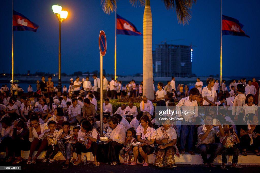 People eat dinner on a roadside outside the Royal Palace for a ceremony involving King Norodom Sihamoni to finish before police let them onto the grounds to pay their respects to former King Norodom Sihanouk on February 2, 2013 in Phnom Penh, Cambodia. The former kings coffin was transported to the cremation site yesterday after being paraded through the capital in a lavish funeral procession. The cremation will take place on Monday the 4th of February, the funeral pyre will be lit by his wife and son King Norodom Sihamoni.