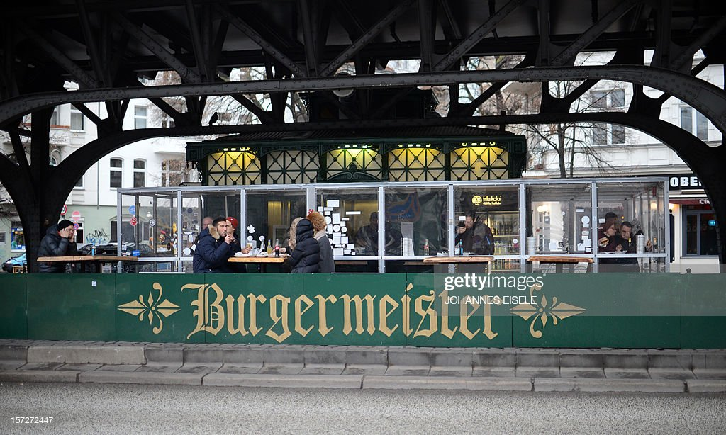 People eat in front of the 'Burgermeister' restaurant in Berlin on December 1, 2012. The restaurant is located in a former public restroom that was redesigned as restaurant six years ago.