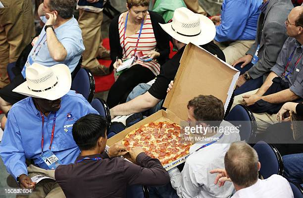 People eat pizza on the arena floor during the start of the Republican National Convention at the Tampa Bay Times Forum on August 27 2012 in Tampa...