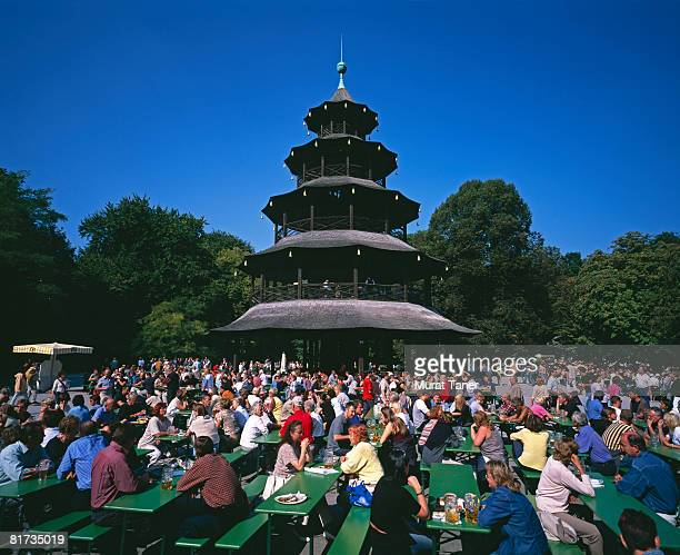 People eating and drinking beer around the Chinese Tower in the English Garden.  Munich, Germany