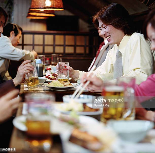 People eating and drinking in restaurant, focus on young man laughing