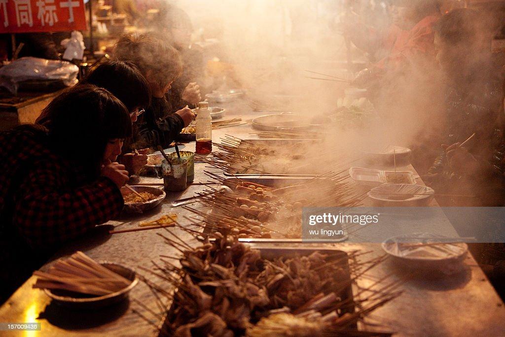 people eating malatang at winter night street.
