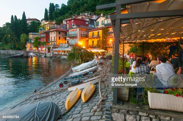 People eating out at dusk in Varenna, Lake Como, Italy.