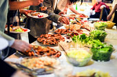 Large group of people picking food (grilled meat and salads) from a buffet table. Unrecognizable Caucasian adults, both female and male.