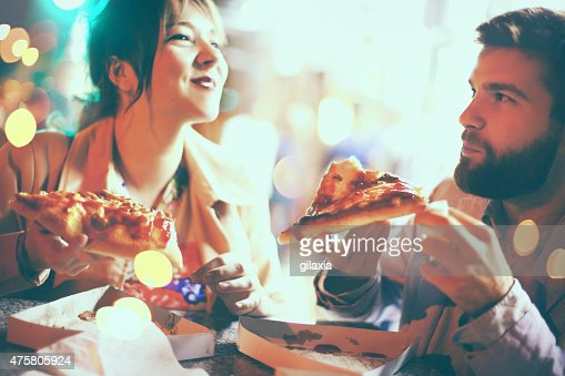 People eating pizza in the street.