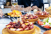 People eating Pulpo a la Gallega with potatoes. Galician octopus dishes. Famous dishes from Galicia, Spain.