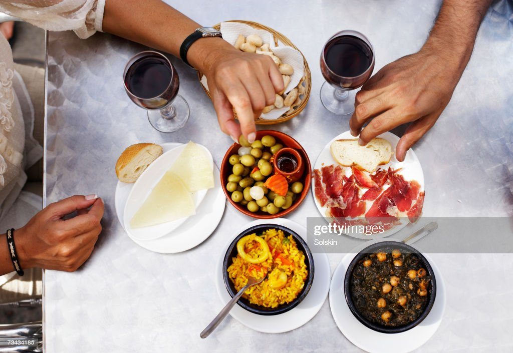 People eating tapas at outdoor restaurant, close-up of hands, overhead view