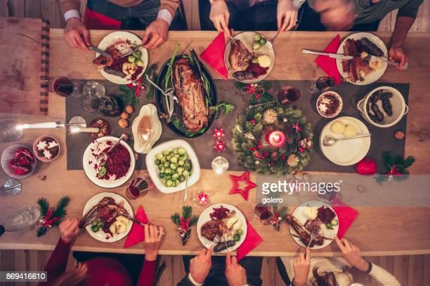 Menschen, die traditionelle Weihnachtsessen an festlichen Holztisch essen