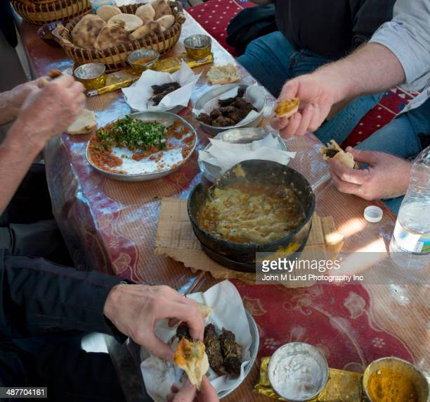 People eating Yemeni food at table, Saana, Yemen
