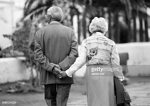 people elder people older couple walking hand in hand holding hands suit blouse skirt aged 65 to 75 years Spain Canary Islands Canaries Puerto de la...