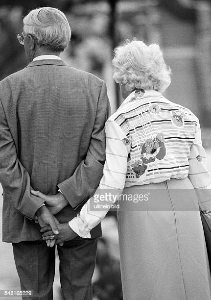 people elder people older couple walking hand in hand holding hands suit blouse skirt aged 65 to 75 years Spain Canary Islands Canaries Tenerife...