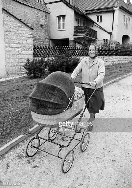 people elder people older woman walking with a buggy waistcoat skirt kerchief aged 70 to 80 years
