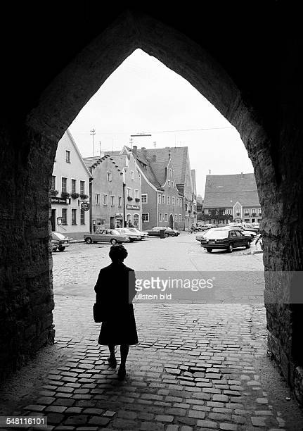 people elder woman walks through a town gate to the market place residential buildings backlight silhouette aged 65 to 75 years DBerching Altmuehl...