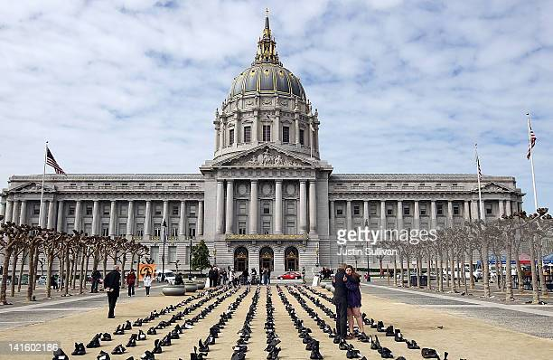 People embrace as they stand among rows of combat boots that are part of the 'Eyes Wide Open' exhibit in front of San Francisco City Hall on March 19...