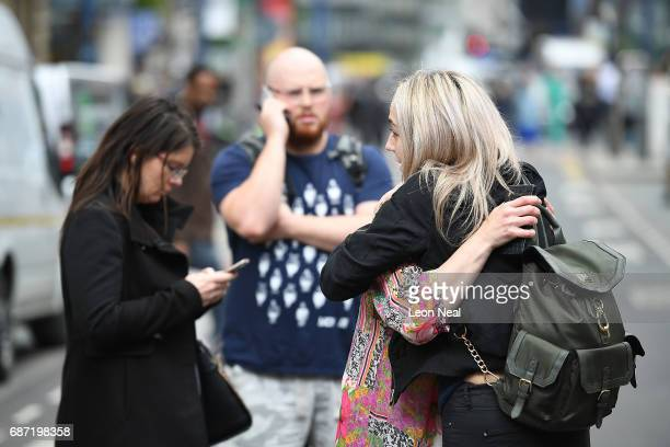 People embrace as they stand near the Arndale centre on May 23 2017 in Manchester England Prime Minister Theresa May held a COBRA meeting this...