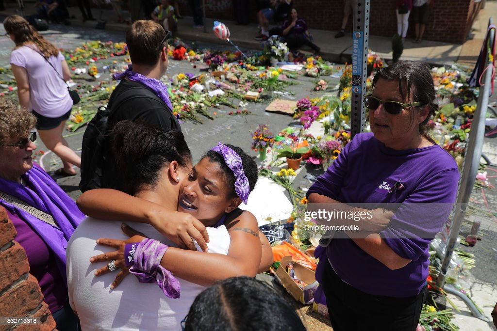 People embrace at the spot where Heather Heyer was killed and 19 others injured when a car slammed into a crowd of people protesting against a white supremacist rally, August 16, 2017 in Charlottesville, Virginia. Charlottesville will held a memorial service for Heyer Wednesday, four days after she was killed when a participant in a white nationalist, neo-Nazi rally allegedly drove his car into the crowd of people demonstrating against the 'alt-right' gathering.