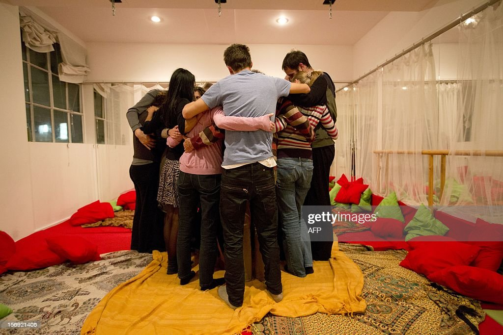 People embrace during a 'Cuddle Workshop' in London on November 4, 2012. The lilting beat of 'Don't Worry, Be Happy' sets the tone. Green and red scatter cushions fill the floor and nervous strangers sit around awkwardly, preparing to get up close and personal at a 'cuddle workshop'. Organiser Anna Nathan announces the rules in a comforting voice. 'You don't have to do anything you don't want to do,' the 36-year-old tells the two dozen men and women sat round in a circle in a dance studio in north London. AFP PHOTO / JUSTIN TALLIS
