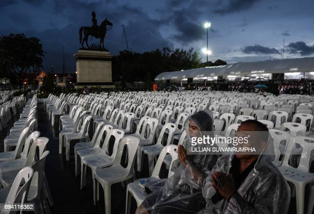 People endure the rain to pray during a Buddhist ceremony for the late Thai King Bhumibol Adulyadej at the King Rama V Monument in Bangkok on June 9...