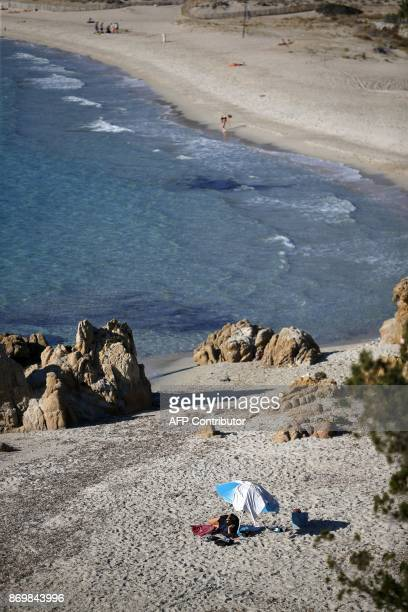 People enjoy a day at the beach close from Coti Chiavari on November 3 2017 on the French Mediterranean Island of Corsica / AFP PHOTO / PASCAL...