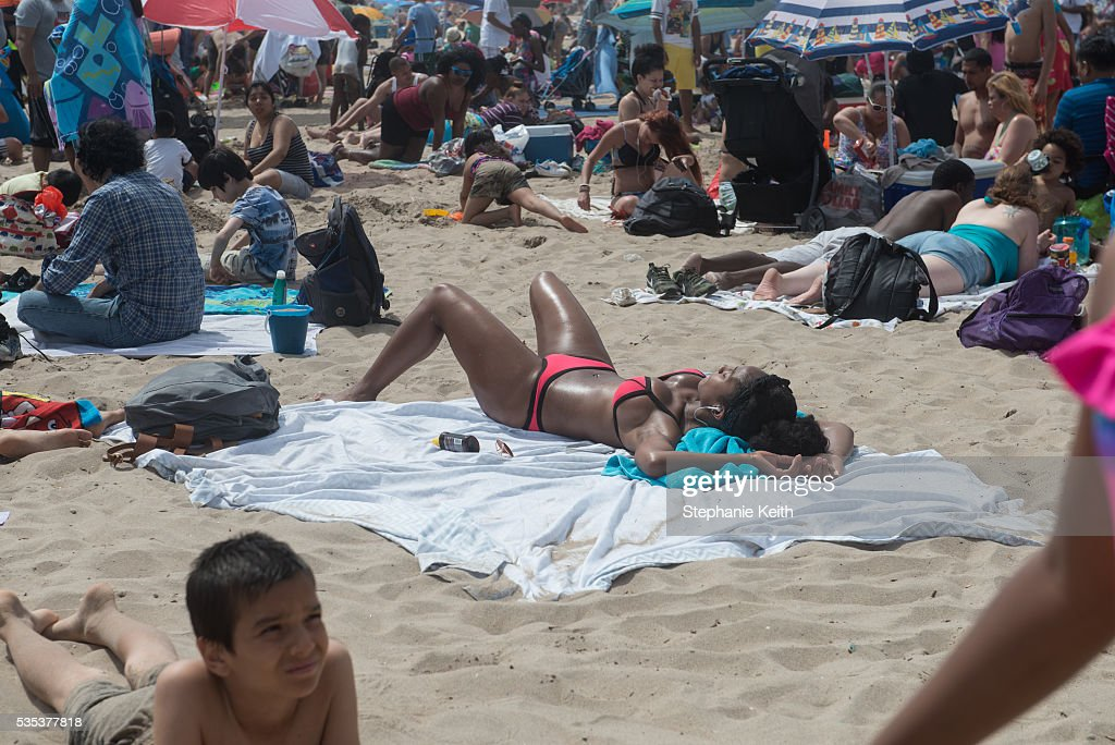 People enjoy a day at the beach in Coney Island on May 29, 2016 in the Brooklyn borough of New York City. New York City is experiencing higher than average temperatures for the holiday weekend.