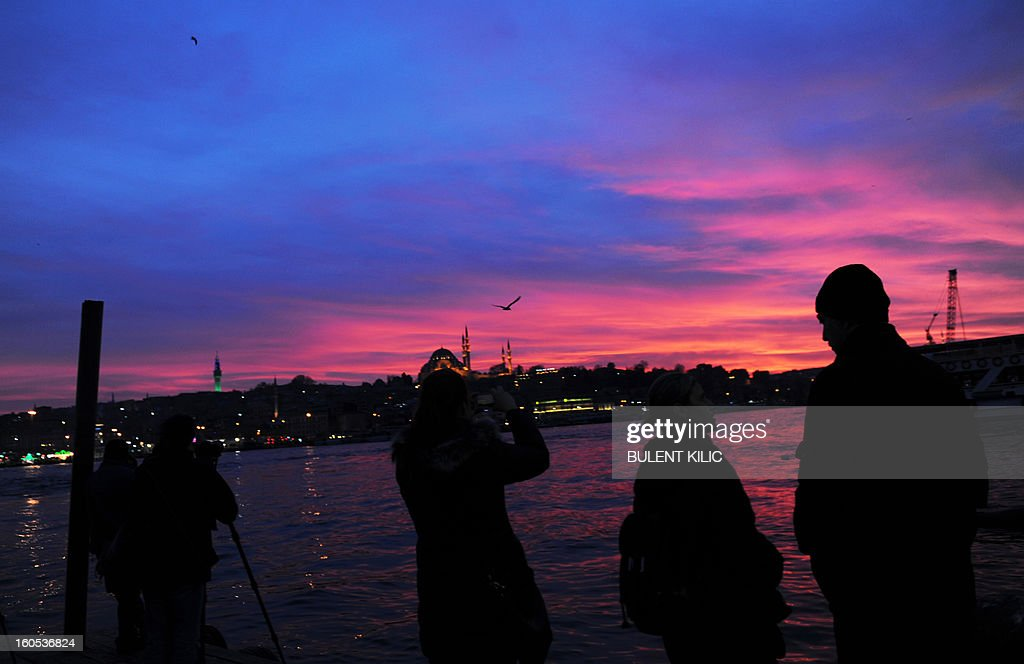 People enjoy a day during sunset over Goldenhorn, on February 2, 2013, in Istanbul. In the background is seen Yeni Camii (New Mosque).