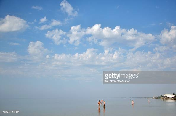People enjoy a day out at the beach in the Black Sea port of Skadovsk southern Ukraine on September 21 2015 AFP PHOTO / GENYA SAVILOV
