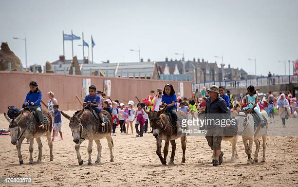 People enjoy a donkey ride as visitors to the beach enjoy the fine weather on June 11 2015 in WestonSuperMare England Many traditional British...