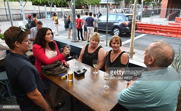 People enjoy a drink in a bar as an official car enters the security cordon surrounding the Southbank precinct where the G20 Summit will be held in...