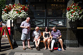 People enjoy a drink outside the Red Lion pub on Whitehall Westminster on July 18 2016 in London England London enjoyed warm weather today with...