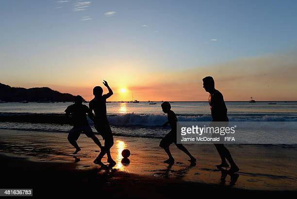 People enjoy a game of football on Coco beach in Liberia on March 30 2014 in Liberia Costa Rica