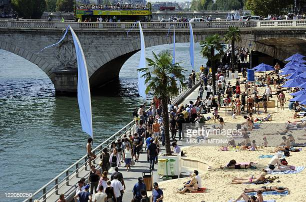 People enjoy a sun bath or a walk on the banks of the river Seine on August 21 2011 in Paris on the last day of 'Paris Plages' the ephemeral beach...