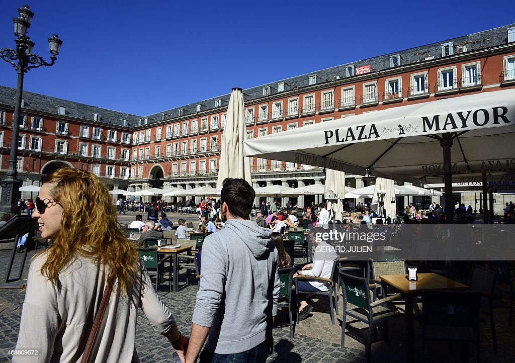 People enjoy a sunny day on terraces of the Plaza Mayor in the historical centre of Madrid on April 4 2015 AFP PHOTO/ GERARD JULIEN