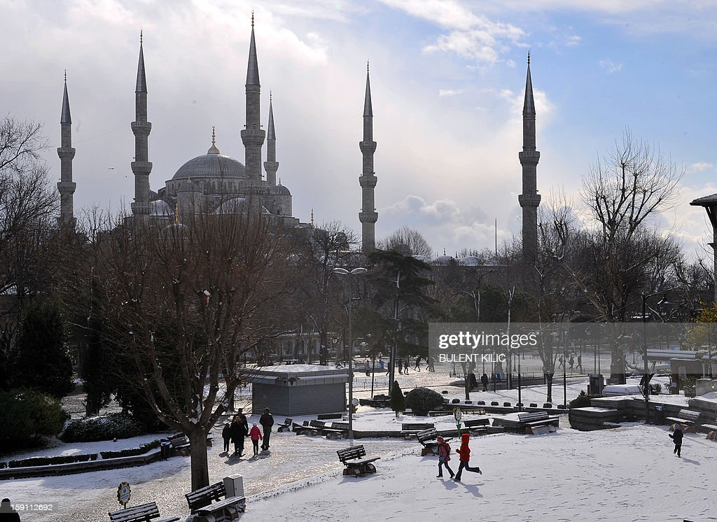 People enjoy a walk in the snow covered Sultanahmet square in Istanbul on January 8, 2013. Heavy snowfall blanketed Turkey's commercial hub Istanbul, a city of 15 million, paralysing daily life, disrupting air traffic and land transport. Officials said the snow is expected to continue until late tomorrow, according to the weather forecast.
