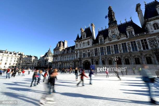 People enjoy at a temporary iceskating rink set up in front of the Paris city hall for the Christmas and New Year celebrations in Paris France on...
