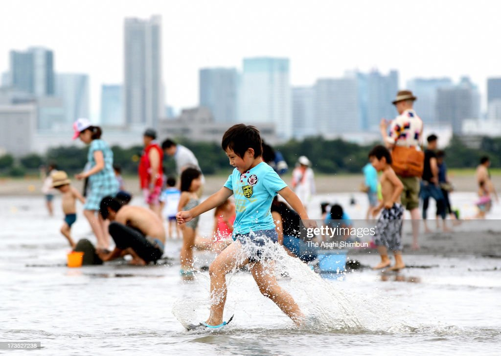 People enjoy bathing at the sea during a beach opening at Kasai kaihin Park on July 15, 2013 in Tokyo, Japan. A local non-profitable organization has tackled to water quality improvement at Tokyo Bay for more than 30 years, and managed to reach an agreement with Tokyo Metropolitan government to open the beach, for the first time in almost 50 years.
