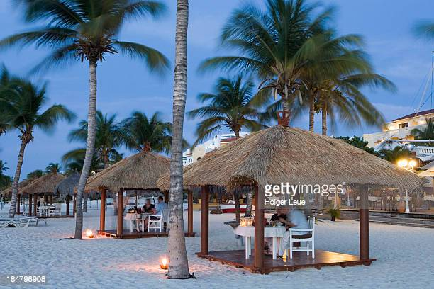 People enjoy beach dinner in palapa huts at dusk