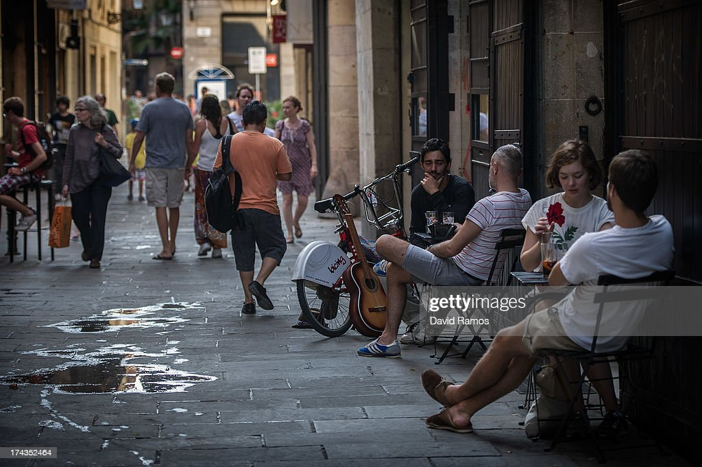 People enjoy drinks outside a bar on July 24, 2013 in Barcelona, Spain. Foreign visitors to Spain set a new record high in June surpassing six million tourists for the first time ever and climbing by 5.3 percent since June 2012.Ê