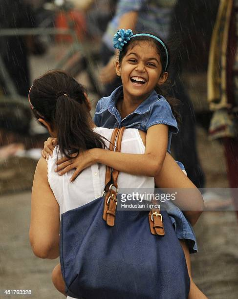 People enjoy during a cloudy weather and sudden rain on July 6 2014 in Noida India Delhi experienced a warm day but rain in the evening brought...