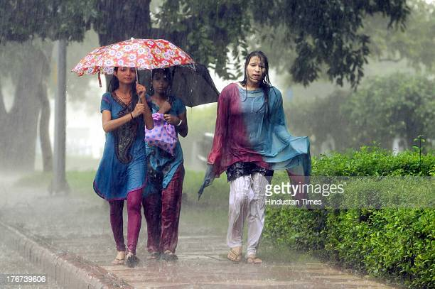 People enjoy during heavy rain at India Gate lawns on August 18 2013 in New Delhi India Heavy rainfall lashed the National Capital Region on flooding...