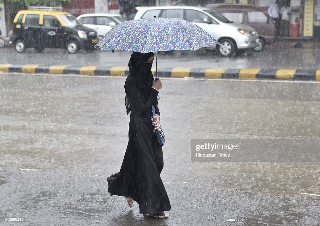 People enjoy during heavy rain, on June 24, 2016 in Mumbai, India. Rains continued to lash Mumbai for the third consecutive day today, slightly disrupting suburban train services, even as the Met department predicted heavy showers. India Meteorological Departments Regional Meteorological Centre in Mumbai predicted intermittent rain with heavy to very heavy rainfall at a few place in the city and its suburbs for the next 24 to 48 hours.
