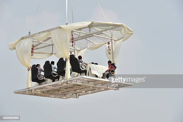 People enjoy free launch at a dinner table lifted into sky by a crane on September 24 2015 in Hefei Anhui Province of China The event is launched by...