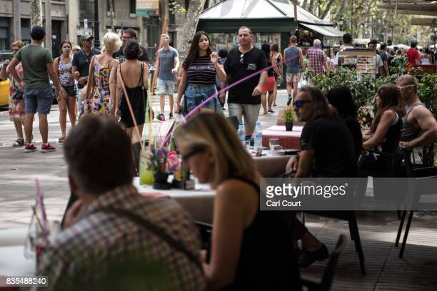 People enjoy lunch as others walk past on Las Ramblas as life returns to normal following Thursday's terrorist attack on August 19 2017 in Barcelona...