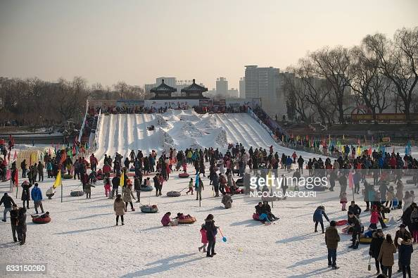 People enjoy playing with snow in an amusement fair inside a park during the Spring Festival holidays in Beijing on January 31 2017 Millions of...