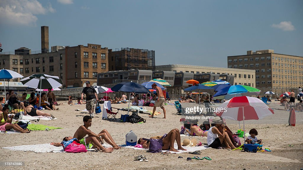 People enjoy Rockaway Beach during a heat wave on July 17, 2013 in the Rockaway Beach neighborhood of the Queens borough of New York City. Temperatures have been reaching 100+ degrees throughout the New York City area; temperatures are expected to stay high through the end of the week.