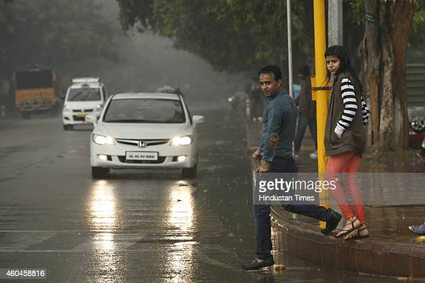 People enjoy sudden rain on a cold and foggy day at India Gate on December 14 2014 in New Delhi India The weatherman said that the chill was only...