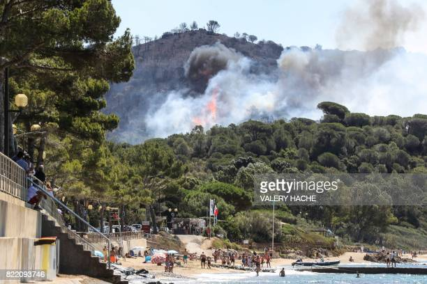 TOPSHOT People enjoy the beach as a fire burns a forest by the sea in La CroixValmer near SaintTropez southern France on July 25 2017 Firefighters...