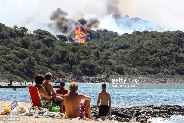 TOPSHOT People enjoy the beach as they look at a forest fire in La CroixValmer near SaintTropez on July 25 2017 Firefighters battle blazes that have...